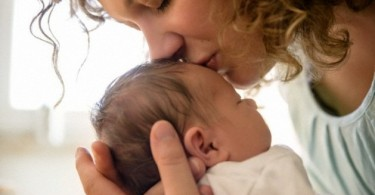 Mother kissing newborn baby boy (0-1 months) --- Image by © Buero Monaco/Corbis