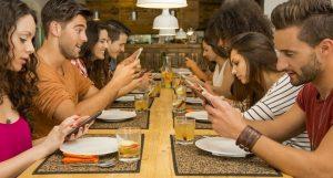Uomini e donne al tavolo con dipendeza da facebook e smartphone